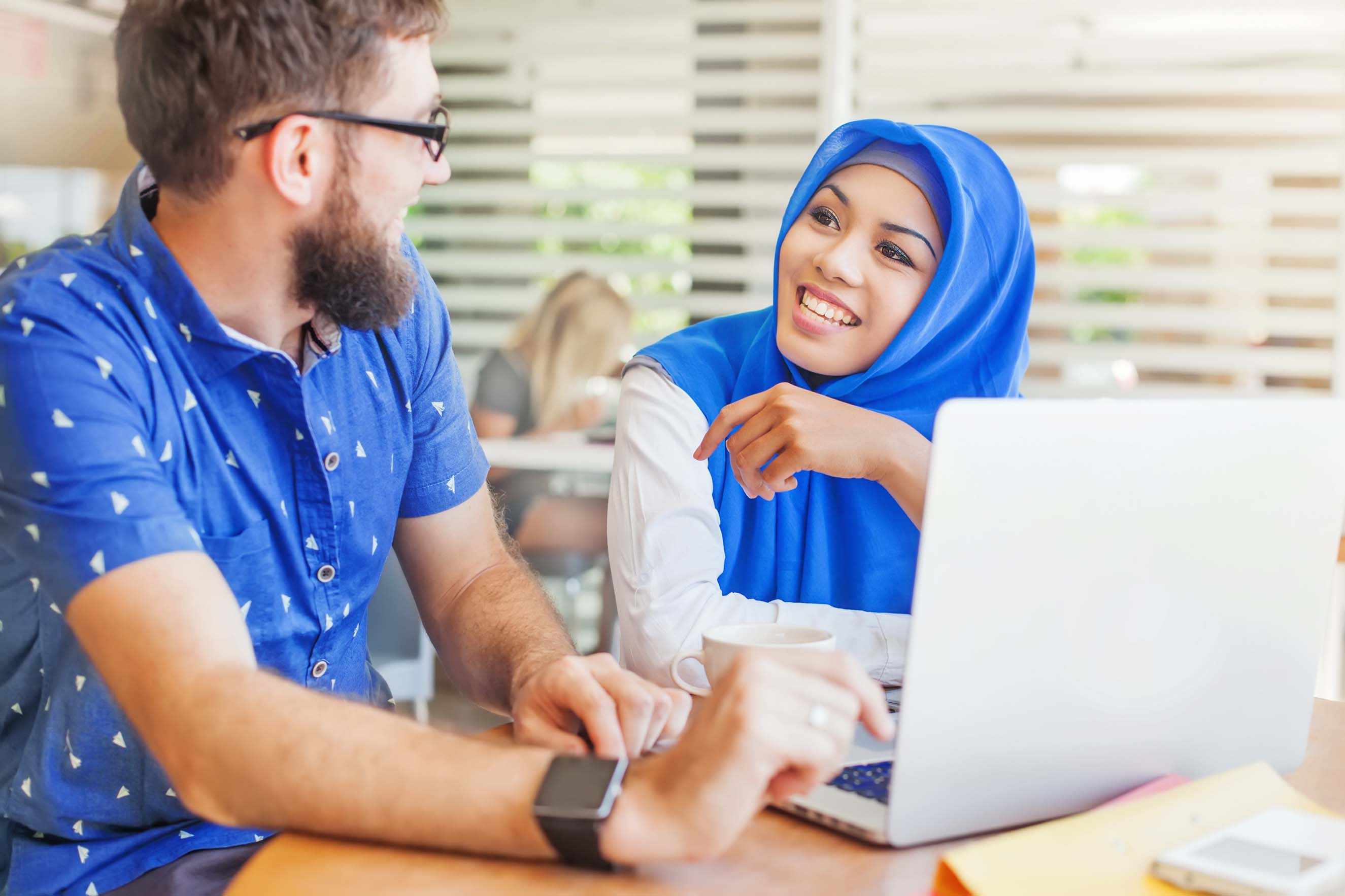 asian muslim woman and caucasian man looking at screen of laptop